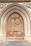 Detail of wooden door and stone arched entrance to the abbey church, Bath, Somerset, England