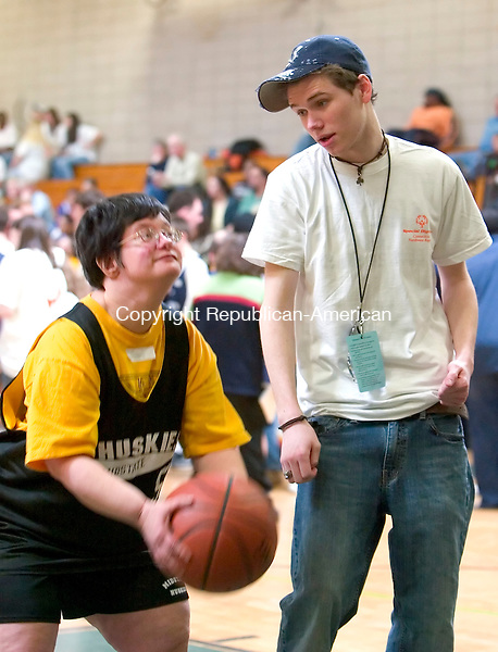 WATERBURY, CT--24 MARCH 2007--032407JS07-Volunteer Eamon Downey, right, gives pointers to Special Olympian Maria Duval ball during the individual skills competition at the Special Olympics Connecticut-Northwest Region's 2007 Traditional Basketball Invitational held at Holy Cross High School in Waterbury. The tournamnet was held at a total of five schools in the city of Waterbury.