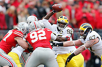 Michigan Wolverines quarterback Devin Gardner (98) gets taken down Ohio State Buckeyes defensive lineman Adolphus Washington (92) and Ohio State Buckeyes defensive lineman Joey Bosa (97) in the second quarter the college football game between the Ohio State Buckeyes and the Michigan Wolverines at Ohio Stadium in Columbus, Saturday morning, November 29, 2014. As of half time the Ohio State Buckeyes and Michigan Wolverines were tied 14 - 14. (The Columbus Dispatch / Eamon Queeney)