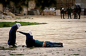 Jerusalem, Israel<br /> January 15, 1988<br /> <br /> Two Palestinian women aid a victim after clashes with Israeli soldiers at the Dome of the Rock mosque. <br /> <br /> Israeli soldiers move into the Dome of the Rock as Palestinians shout anti-Israeli slogans and burn Israeli and American flags after Friday ceremonies. Israel soldiers shoot tear gas into the Dome as young Palestinians throw rocks at the soldiers. Several police and at least 70 Palestinians are injured as the Israelis beat Palestinians with clubs during the 1 hour ordeal.