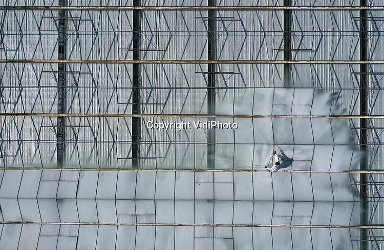 Foto: VidiPhoto<br /> <br /> BEMMEL - Om de potplanten in de 27.000 vierkante meter grote kas van Handelskwekerij Kregting op kassengebied NextGarden in Bemmel te beschermen tegen de felle zon, krijgt het glasdak maandag een laagje witte kalk. Dankzij felle zon en wind droogt de kalklaag nu extra snel. Voor de 'witmakers' Frank en Berry Kuster is het nog ouderwets handwerk. Vanaf de eerste week van april zijn ze al bezig om de kassen aan de zonzijden te witten. April was de meest zonnige maand tot nog toe, in tegenstelling tot vorig jaar toen de kassen pas eind april behandeld konden worden. De witte kalklaag reduceert zonlicht en warmte en voorkomt dat gewassen verbranden of verhit raken. De kalklaag, die met een druk van 40 bar wordt gespoten, is biologisch afbreekbaar en wordt na de zomer weer verwijderd.