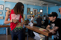 Jun. 10, 2013; Phoenix, AZ, USA: Phoenix Mercury center Brittney Griner shows a tattoo to artist Jason Anthony inside the Golden Rule Tattoo shop in downtown Phoenix. Mandatory Credit: Mark J. Rebilas-