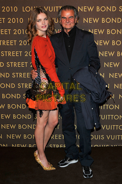 NATALIA VODIANOVA & PATRICK DEMARCHELIER.attends the launch of the Louis Vuitton Bond Street Maison in London, England, UK, May 25th, 2010. .full length red dress polka dot sleeve long sleeved orange black clutch bag gold shoes grey gray suit trainers side .CAP/PL.©Phil Loftus/Capital Pictures.