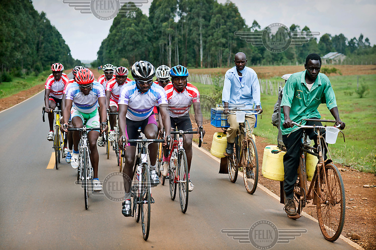 The Kenyan National Cycling Team pass local milk vendors also on bicycles as they train along a road between Eldoret and Iten. The team is managed by Singaporian Nicholas Leong and trained by Australian Simon Blake.
