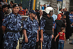 Palestinian Policemen stand guard as employees paid by the Palestinian Authority wait to receive their salaries outside a closed bank after a scuffle with employees appointed by Hamas since 2007, in Gaza City June 5, 2014. A Palestinian unity government formed by President Mahmoud Abbas and the Islamist Hamas group faced its first and serious challenge on Thursday when civil servants of Hamas, who were not on a payment list, scuffled with those cashing their salaries. Civil servants employed by Hamas since 2007 arrived and prevented employees paid by the Palestinian Authority from receiving their salaries, vowing either both get paid or no one does. Photo by Ashraf Amra