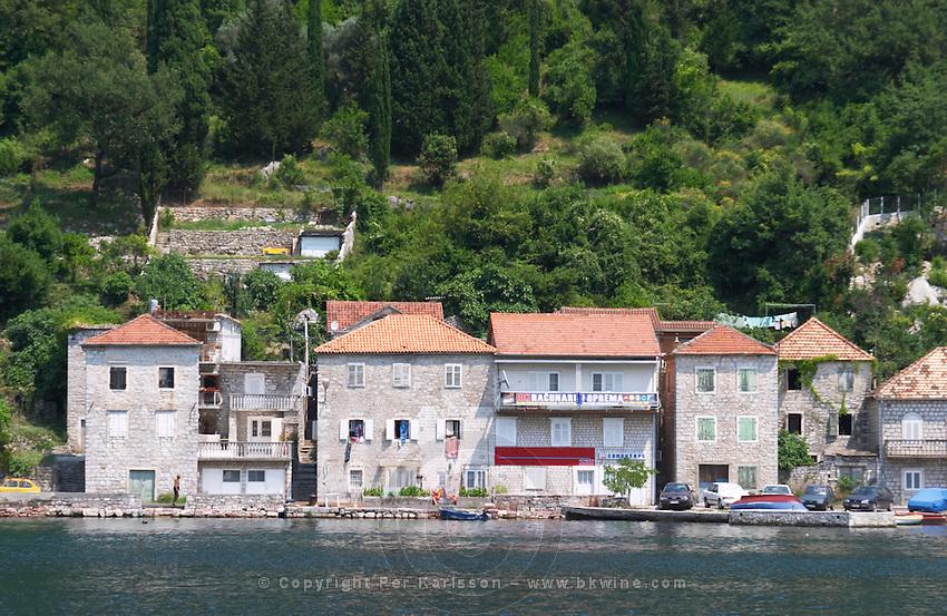 Stone houses along the water edge in Lepetani. Montenegro, Balkan, Europe.