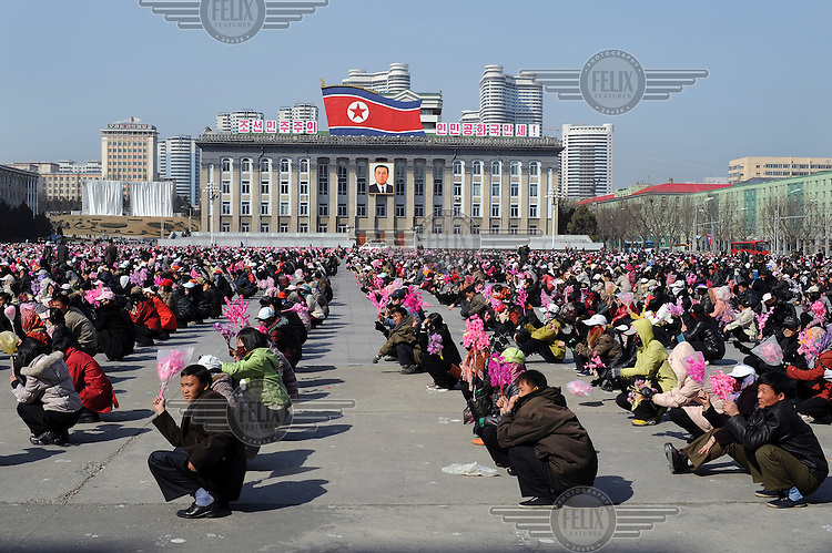 Young men and women waiting on Kim Il-sung Square to rehearse a display for celebrations marking the 100th birthday of Kim Il-sung....