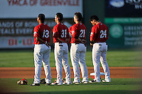 Infielders Rafael Devers, left, Javier Guerra, Nick Longhi and Yoan Moncada of the Greenville Drive stand for the National Anthem before a game against the Charleston RiverDogs on Friday, August 14, 2015, at Fluor Field at the West End in Greenville, South Carolina. Charleston won 6-2. (Tom Priddy/Four Seam Images)