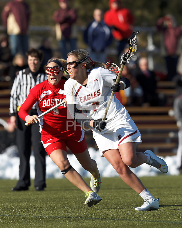 Boston College attacker Covie Stanwick (8) on the attack as Boston University defender Christie Hart (9) defends..Boston College (white) defeated Boston University (red), 12-9, on the Newton Campus Lacrosse Field at Boston College, on March 20, 2013.