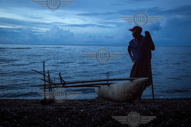 Eliuda Toxok, a shark caller from Messi village, prepares to go to sea in his outrigger canoe. Shark calling is the ancient tradition among the fishermen of New Ireland. They paddle into the Bismarck Sea where they make a noise, hitting water with a tool called a 'larding' which is made of coconut shells. This mimics the sound of a school of fish thrashing on the surface of the water, thereby 'calling' nearby sharks. When a shark comes close, the fisherman ensnares it using a 'ka'saman', a propeller-shaped float with a noose of twisted vine looped through it. The Shark population is under threat from ocean acidification, sea bed mining and commercial fishing for their fins.