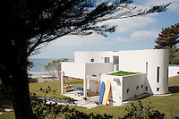 This contemporary beach house occupies the site of an old stone cottage and overlooks a sandy beach with a 180 degree view of the sea