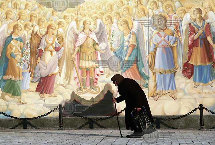 An old woman walking past a mural depicting a scene from the Holy Bible, at the entrance to the Mykhailivsky Golden Domed Cathedral in central Kiev.