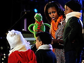 """First Lady Michelle Obama reads """"The Night Before Christmas"""" with Kermit the Frog during the 2011 National Christmas Tree Lighting on the Ellipse in Washington, DC, on Thursday, December 1, 2011.     .Credit: Roger L. Wollenberg / Pool via CNP"""