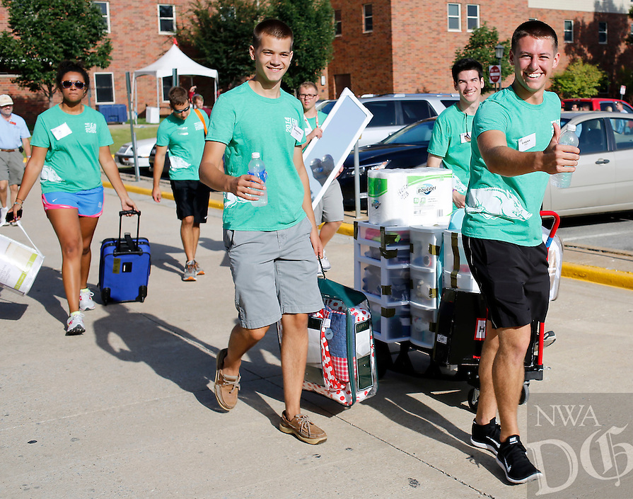 NWA Media/DAVID GOTTSCHALK - 8/20/14 - Logan Kiihnl (cq), right, leads a group of volunteers pulling a cart with belongings Wednesday August 20, 2014 in front of Hotz Honors Hall on the campus in Fayetteville. Wednesday was Assisted Move-In Day for the Universtiy of Arkansas students. Move in started this past weekend with more than 5,000 students moving into residence halls this week.
