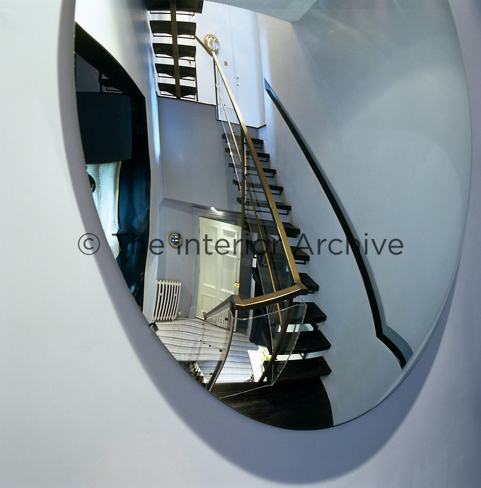 The reflection of the staircase can be seen in a large convex mirror placed on a landing to maximise the available space and light