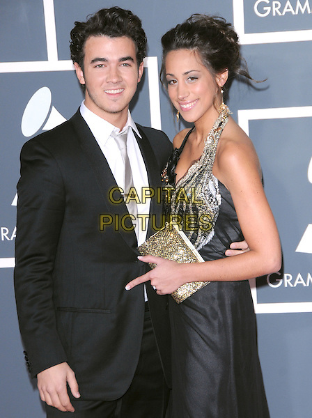 KEVIN JONAS (JONAS BROTHERS) & DANIELLE DELEASA.Arrivals at the 52nd Annual GRAMMY Awards held at The Staples Center in Los Angeles, California, USA..January 31st, 2010.grammys half length black suit jacket dress silver gold sequins sequined clutch bag halterneck married husband wife .CAP/RKE/DVS.©DVS/RockinExposures/Capital Pictures