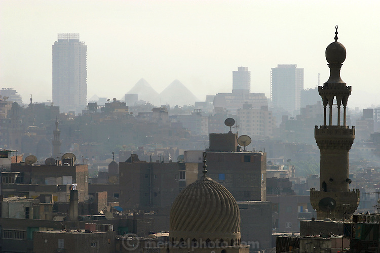 The pyramids of Giza as seen through the dust, smoke and haze of Cairo Egypt from the minaret of a mosque in old Cairo.