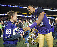 Brandon Lewis gives a young fan his gloves following Washington's big win over Stanford.