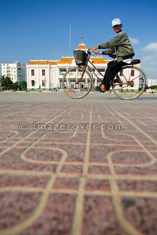 "Asia, Vietnam, Nha Trang. Cycling past ""Nha Van Hoa"", Nha Trang's Vietnamese Cultural House located at the beach promenade Tran Phu."