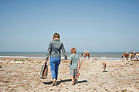 A woman and child walk hand in hand on a beach towards the sea.