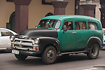 Havana, Cuba; a green and black classic 1950's Chevy Suburban, serving as a taxi, driving down the street in Havana