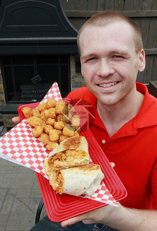 Jacobsmeyers Tavern in Granite City. Here, cook Jake Ritchie displays a popular dish, buffalo chicken wrap with tater tots. He is seated by a free-standing fireplace in the beer garden.