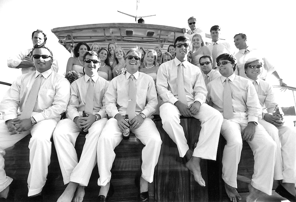 Black & white shot of bridal party on the deck of a boat.