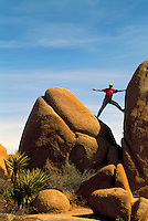 Woman climbing / balancing on a Rock, Joshua Tree National Park, California, USA (Model Released)