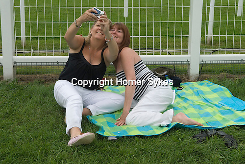Friendship. Ladies Day at the Derby horse race. Epsom Down Surrey UK. 2012