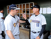 Manager Al Pedrique (13) of the Charleston RiverDogs, right, speaks with hitting coach P.J. Plittere (31) prior to a game against the Greenville Drive on Saturday, April 6, 2013, at Fluor Field at the West End in Greenville, South Carolina. Charleston won Game 1 of a doubleheader, 6-2. (Tom Priddy/Four Seam Images)