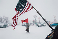 "Two nations - Veterans carry an American and a Mohawk Warrior Society flag through the storm. The Mohawk flag came to prominence during the 1990 Canadian Oka Crisis, when the military confronted indigenous people in a major armed conflict for the first time in modern history. Camp is dedicated to stopping the Dakota Access Pipeline (DAPL) ""in a good way"" but there is some fear history will repeat itself, again."