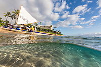 An over-and-under image of Ka'anapali Beach and a Hawaiian sailing canoe, Maui.