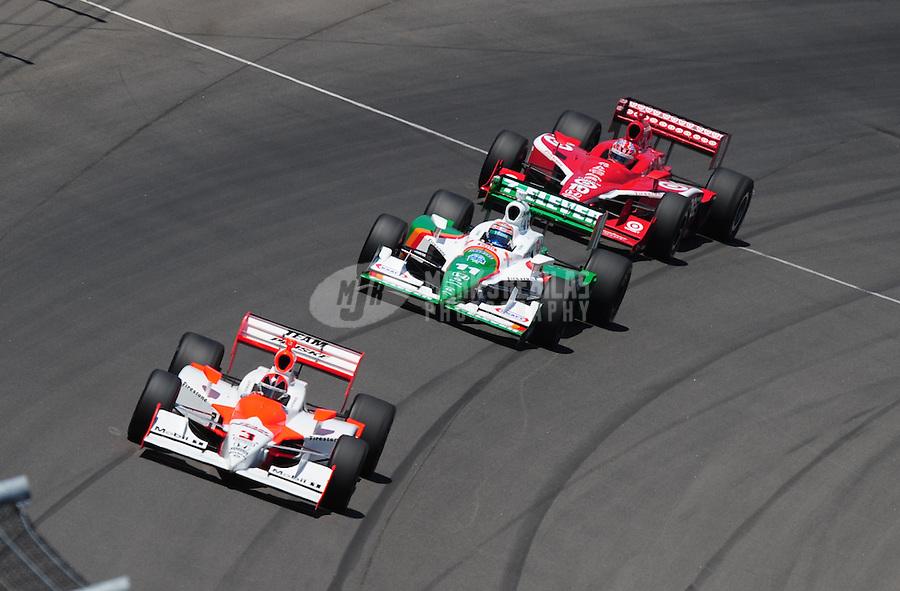 Jun. 22, 2008; Newton, IA, USA; IRL driver Helio Castroneves (3) leads Tony Kanaan and Dan Wheldon during the Iowa Corn Indy 250 at the Iowa Speedway. Mandatory Credit: Mark J. Rebilas-