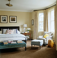 A velvet upholstered bench piled with books is placed at the foot of the double bed in the master bedroom