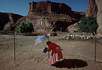 A native woman keeps in the shade of her umbrella while letting her sheep out of the peb in Canyon De Chelly National Park.  The park serice has a cooperative agreement with the native community in running the park.