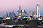 An updated 2012 Charlotte NC skyline photo as the sky was lit with the color from the sunset. Charlotte NC makes a great skyline photo, and a great way to represent the Queen City. The skyline has changed and grown incredibly over the last few years, so if youre using a blurry, or outdated Charlotte skyline photo, consider what that says, and upgrade to a high quality skyline photograph. You will not find many photos taken from this angle with the streaming tailights in the foreground, as many photographers are forced to take this shot from street level, where there are many obstructions, and this foreground is not visible.