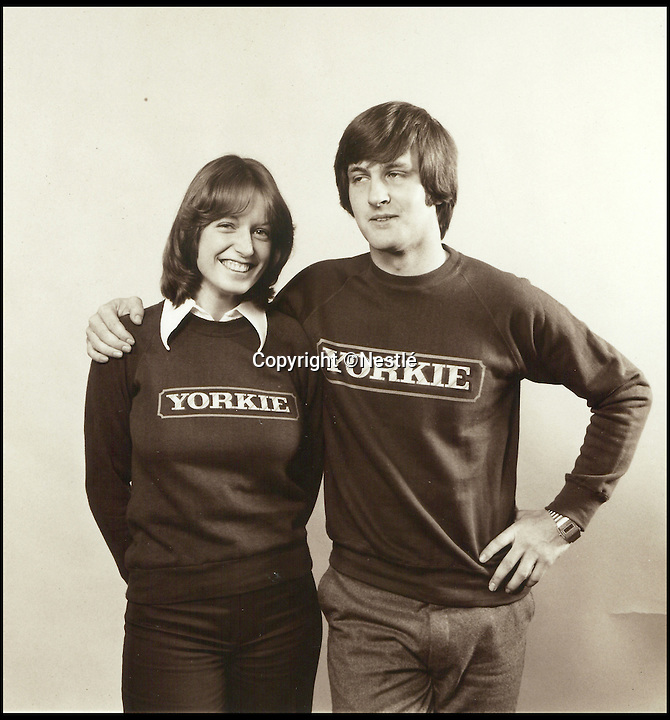BNPS.co.uk (01202 558833)<br /> Pic: Nestlé/BNPS<br /> <br /> Two models wear Yorkie jumpers.<br /> <br /> As one of the UK's most popular chocolate bars celebrates its 40th birthday, unseen archive images of the alternative bars that could have been launched instead have been revealed.<br /> <br /> The Yorkie bar became one of the UK's top ten selling confectionery within a year of being launched and now 85.7 million are made every year.<br /> <br /> But in 1976 Rowntree considered several other 'aspirational' sweets, including a port flavoured one, before opting for the chunky chocolate snack.<br /> <br /> Rowntree Mackintosh, which already produced Kit Kat and Aero, decided to launch a new product to get into the solid chocolate bar sector and compete with Cadbury's Dairy Milk and Mars' Galaxy.<br /> <br /> Nestlé UK, who bought the brand as part of Rowntree Mackintosh in 1988, have uncovered a portfolio of artwork that reveals all the ideas and the now famous bar's original name - Rations.