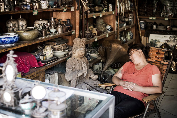 """A Chinese seller takes a rest in her memorabilia and ancient souvenirs' shop in PingYao, China, July 29, 2014. <br /> <br /> This image is part of the series """"24/7"""", an ironic view on restless and fast-growing Chinese economy described through street vendors and workers sleeping during their commercial daily activity. <br /> <br /> © Giorgio Perottino"""
