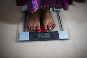A woman stands on the weighing scale at the general OPD of the Duncan Hospital in Raxaul, Bihar, India.