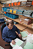 Man with numeracy and literacy disability and learning difficulties working as microfilm technician in visual communications office,