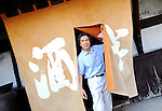 "Yasutaka Daimon, president and owner of Daimon Sake Brewery Co., walks through the ""noren"" curtain at the entranceway to his Sakahan brewery in Mukune Village, Osaka, Japan on July 24 2008. Daimon is the 6th generation master brewer at Sakahan, which has been in existence for the best part of two centuries. Sakahan is a key exporter of sake, a wine-like alcoholic beverage fermented from rice, particularly to the U.S. where his popular Mukune brand is available in 44 states...Photographer: Robert Gilhooly"