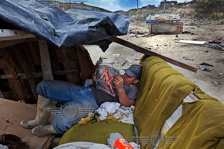 A worker at a rubbish dump reads a magazine as he takes a break.