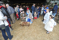 NWA Media/Michael Woods --12/21/2014-- w @NWAMICHAELW...Zach and Kelsey Ayres playing the role of Mary and Joseph listen to the angels sing, played by Leighann Talbert age 5 (right) and Kamy Strauss, age 8, sing as visitors walk through the living nativity at the Bella Vista Christian Church Sunday evening in Bella Vista.  It is the second year for the church to offer the live nativity to the community, with a new feature of  live camels for this years display.