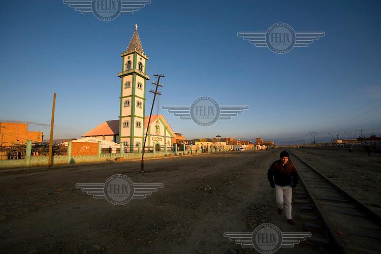 A man walks beside a railway line past a church in El Alto.