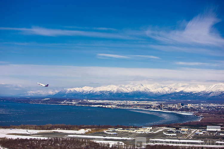 Aerial photo of a plane taking of from Ted Stevens International Airport with Downtown Anchorage and the Chugach Mountains in the background, taken from the West, late winter, Southcentral Alaska, USA.