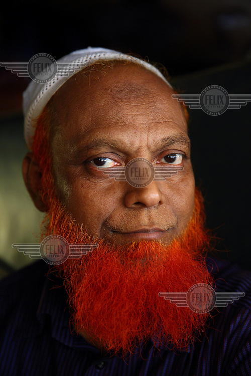 An old man who dyed his hair and beard with Henna.<br /> <br /> It is very common in Bangladesh to see older people with dyed orange hair, men with orange beards or orange moustaches and women with orange hair. The dye used is from the flowering Henna plant. The practice comes from the widely held belief that the Prophet Muhammad dyed his beard and hair. It is also common among people returning from Hajj. Some Muslims believe that henna is the only dye they are free to use for colouring their hair.