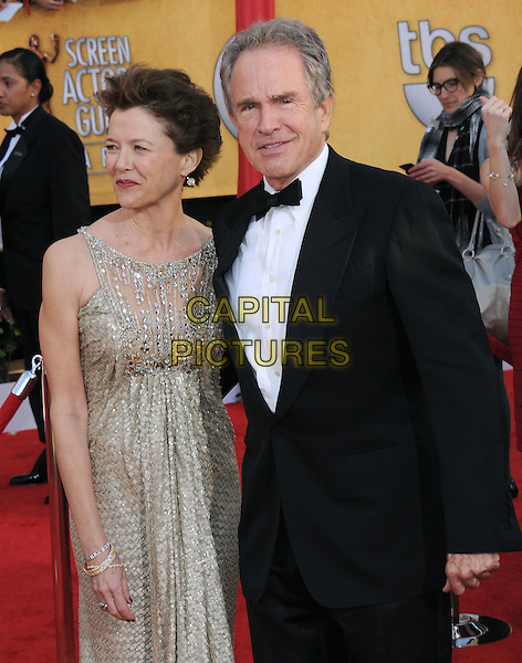 ANNETTE BENING & WARREN BEATTY.17th Annual Screen Actors Guild Awards held at The Shrine Auditorium, Los Angeles, California, USA..January 30th, 2011.arrivals SAG half length dress beige black white tuxedo married husband wife sleeveless beads beaded gold.CAP/RKE/DVS.©DVS/RockinExposures/Capital Pictures.