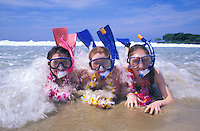 Girls with snorkel gear wearing leis play in ocean surf Hawaii