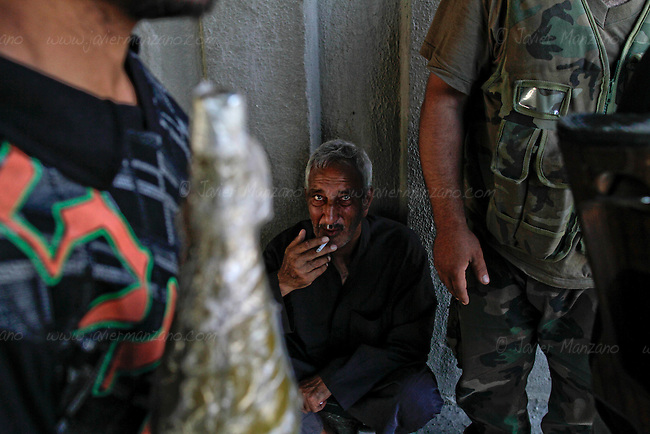A civilian is briefly questions by Free Syrian Army soldiers as he was seen wandering around the frontline of Al Qoob in the heart of Aleppo city. ..© Javier Manzano