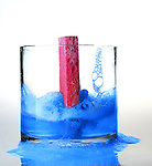 Pink Sponge falling into Blue colored Soapy Water in Glass Bowl